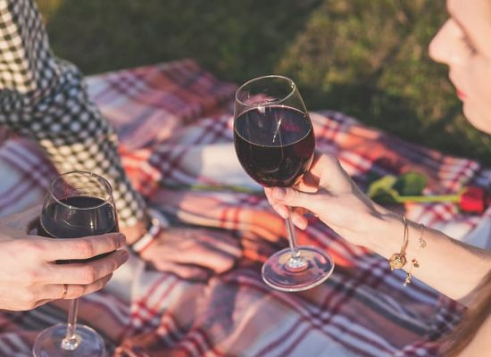 two-people-holding-clear-wine-glasses-during-daytime